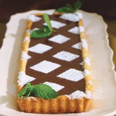 1 rolled-out rectangle of basic tart dough   1 1⁄2 cups heavy cream  8 to 10 fresh mint sprigs (about 40 leaves),   plus sprigs for garnish  12 oz. semisweet chocolate, chopped into   small slivers  2 Tbs. light corn syrup  Confectioners' sugar or unsweetened cocoa   powder for dusting