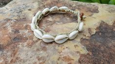 Super beautiful and comfortable, this anklet would be the perfect accessory for a beach wedding!! This anklet is tied with natural Romanian hemp and measures 9.5 inches around and has a nice wood disk bead and loop closure. Ive tied smooth beautiful cowrie shells all the way around..... so pretty :-) If you have any questions please dont hesitate to message me!! I love to do custom pieces :-) ***Respect your hemp jewelry! If you want it to last try not to get it wet more than once!! Shipp...
