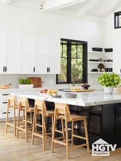 Christina Anstead's Cali-cool kitchen features a large marble-top island, open shelving and light wooden bar stools. Take a full tour.