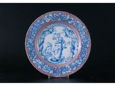 A rare Delft plate, painted in blue with Justice with her sword raised, standing upon a condemned figure beneath the motto 'Libertas populi', the powdered manganese border painted in blue with scrolling flowers and leaves, marked 'B' in blue, probably Bristol c.1740, 23cm.    Cf. A Ray, English Delftware, Pottery in the Robert Hall Warren Collection, Ashmolean Museum Oxford, pl.9 for a similar example.