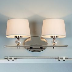 """Gleaming Polished Nickel, crisp crystal spheres, and soft White fabric shades create this modern look with elegant sophistication perfect for updating stylish bathrooms. 2x60 watt max candle base sockets. (8.25""""Hx17""""Wx7.5""""D). Shade (5.5""""x6.5""""x4.5""""). Backplate (4.5""""Hx6.5""""D)."""