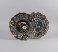 Two Japanese Cloisonne Foliate Chargers, the first with central roundel enameled with a crane, with goldstone accents, the other enameled with reserves of flowers on a black ground, the mouth and foot rims applied with copper, unmarked.