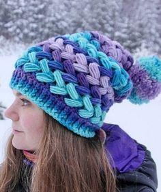 Плетеный узор для шапки Крупный объемный узор для вязания шапки крючком. Освоить этот узор совсем не сложно. В моду давно и прочно вошли объемные шапки. В них тепло и комфортно, и они гармонично смотрятся с верхней одеждой. Эта шапочка связана из пряжи нескольких цветов холодных оттенков: голубой, фиолетовой, синей и сиреневой. Шапка заканчивается разноцветным помпоном. Для вязания шапки вам потребуется крючок №3,5. Большой расход пряжи для шапочки, компенсируется тем что изделие получается…