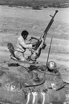 An Iranian soldier loads the machine gun on a Soviet-made tank captured from the Iraqi forces west of Dezful, Iran on Dec. 1, 1982. Even though the Iranians recaptured the area, it is still under constant shelling and attack by Iraqi aircraft. (AP Photo/Ron Edmonds)