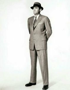 The Man in the Gray Flannel Suit, 1955 by Sloan Wilson. Menswear of the included a suit with less padding in the shoulders and a narrower silhouette. Single breasted styles prevailed and dark gray was the color of choice for the career-minded businessman. Flannel Suit, Grey Flannel, Ny Fashion, Suit Fashion, 1950s Fashion, 1950s Men, 1960s, Penguin Modern Classics, Culture Clothing