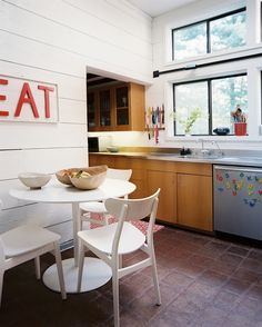 Midcentury Modern Kitchen: A white table and chairs in the corner of a kitchen.