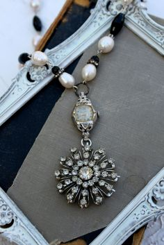 This is interesting.  A watch case with a brooch dangling from it strung on a white and black bead necklace.