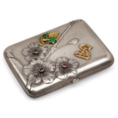 "A FABERGÉ JEWELLLED SILVER CIGARETTE CASE, MOSCOW, 1899–1908. Rounded rectangular form, the lid cast and chased with anemone flowers and buds, embellished with three rubies, and applied with a gold and enamel grape cluster and monogram ""SL""."