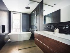 In this bathroom, black tiles create a dramatic touch, and the bath is positioned to take advantage of the view.
