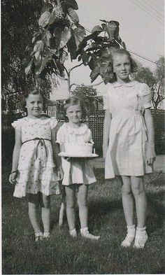 Norma Jeane poses with two younger friends and a birthday cake at about the age of ten.