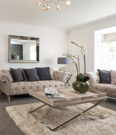 Interior stylist Suzanne Webster chose a classic cream Chesterfield sofa for the lounge, complemented with a cream studded armchair and balanced by the soft, grey carpet and dark, sultry wallpaper.
