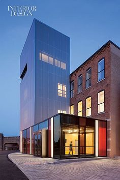 Good Vibrations: SubCat Music Studios in Syracuse | The lobby's glass enclosure intersects with an existing stair and elevator tower, now clad in perforated aluminum. #design #interiordesign #interiordesignmagazine #architecture #buildings #exterior