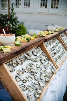 An oyster bar complete with just-shucked oysters, lemon and lime slices, and bowls of mignonette sauce | Brides.com
