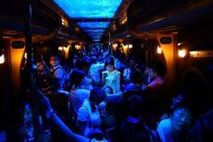 ナショナルジオグラフィック・フォトコンテスト(National Geographic Photo Contest)2014 > 総合優勝 & 人(People)・部門 優勝作品 : 「A node glows in the dark」 混雑した電車の中、誰も存在していないかの様に一人佇む携帯電話を持った女性。