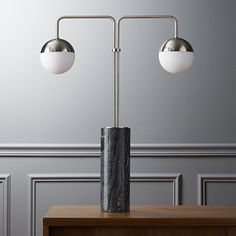 Shop empire table lamp.   Vintage on the top, modern on the bottom.  Brushed nickel double-globe canopy grounds itself in a cylindrical black marble base rich with grey/white marbling.