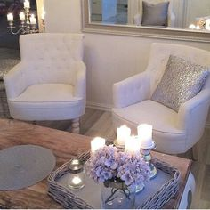 White occasional chairs. Natural wood top coffee table. Tray with candles.