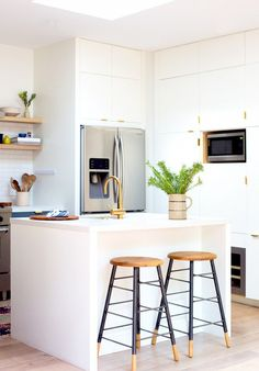 shiny gold hardware on a modern white cabinets. cute wooden island stools too. Home Tour: A Modern Family's Custom Hillside Home via @domainehome