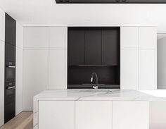   KITCHEN   Beautful way of colour blocking exposed appliances   Induction Cooktop & Wall Ovens. The high-contrast kitchen at Kooyongkoot Road Residence uses white joinery integrating into the walls of open living area and fine-lined, black steel detailing – similar to those used on the external façade. #architecture #melbourne #australia #kitche @distinctjoinery @prmconstructions