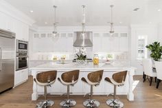 Beautiful kitchen with quartz counter island white cabinets and adjustable height swivel bar stools