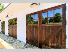 Automated Garage Doors - Three sets of double x garage doors with concealed automatic openers. Glass is neo- restoration, tempered and assembled into insulated glass units (thermopane). First surfaces are natural weathered barn board. Garage Shed, Garage Doors, Garage Design, House Design, Bank Barn, Exterior Doors With Glass, Carriage House, Barn Homes, Lights