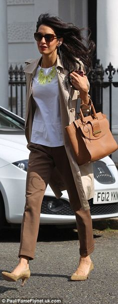 What heatwave? Amal seemed to ignore the heat that descended upon London as she wore a camel trench coat over her white top and browns trousers