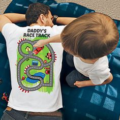 DADDY'S RACE TRACK T-SHIRT Uniquely designed with a race track on the back, Dad gets a soothing back scratch as the kids drive their favorite toy cars along the winding road.