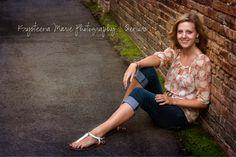 Senior portrait girl sitting at brick wall