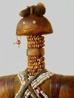 Dowayo (Namchi) fertility doll - Cameroon  ETHNIC GROUP  Dowayo (Namchi)  ORIGIN  North Cameroon  PROVENANCE  Aus der Sammlung Christoph Krüger  MATERIAL  Wood, brass ring, coins, cloth, leather bands, glass beads, seed beads, cowrie shells, brass rings e  SIZE  H: 35 cm
