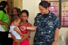 Chief Petty Officer Desma Bishun, assigned to the submarine tender USS Emory S. Land (AS 39), interacts with a woman and her child during a community service assignment at the Olongapo City Women's Center.