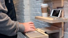StandCrafted minimalist, modular, wall-mounted standing desk with an Apple keyboard and small table module shown in maple hardwood