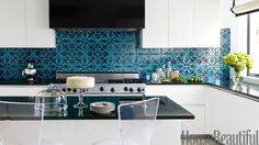 Designers Jeff Lincoln and Hillary Thomas designed the kitchen in a Washington, D.C. town house as a contemporary counterpoint to the rest of the home, which has a '40s French feel. They injected a jolt of color and graphics with a Turkish patterned tile from Ann Sacks and Absolute Black granite countertops.   - HouseBeautiful.com