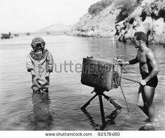 Profile of a young man holding a camera with a scuba diver standing in front of him on the beach by Everett Collection, via ShutterStock