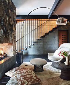 Sala de estar rústica com lareira, móveis assinados e uma bela escada suspensa