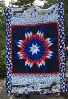 This is a #hockey themed quilt with #Toronto Maple Leaf material for the borders and a #lemoyne star.