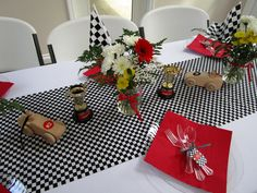 """nascar twins baby shower party décor - tablescape with racecars trophies flowers and cute utensils tied with checker ribbon """"tools""""."""