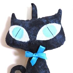 """Pretty black Cat Doll with a big turquoise eyes and a tiny ribbon around the neck that can be removed. This Cat Doll has been designed for decoration, made from my own original pattern and made of 100% high quality cotton and filled with acrylic. You can hang the doll on the wall, put it on a shelf or a sofa and she suitable even for a car or as decoration for your handbag. This black  The cat doll height: 8.3"""" (21cm) The cat doll face width: 4.7"""" (12cm) The cat doll can be gently washed by…"""