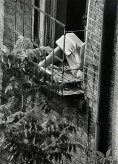 André Kertész, Greenwich Village, New York (woman reading in fire escape window), 1963