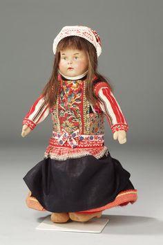 Klederdrachtpop van een meisje uit Marken. 1850-1950 Marker meisje gekleed in daagse dracht, initialen T.P. op boezel en keelband, met ruigie, schort, boezel met wit breitje, de mouwen, rijglijf, slauw, bauw en muts, onderbroek, - kousen en klompen, de pop heeft een kopje van keramiek, echt haar, een lijf van stof. #NoordHolland #Marken