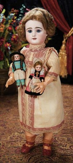 """French Bisque Bebe by Rabery and Delphieu, Signed Rabery Shoes, Miniature Dolls -- Marks: R 1 D. Comments: Rabery and Delphieu, circa 1895. Value Points: with original muslin chemise dress, knit stockings, red kidskin shoes with silk bows signed """"Paris Rabery 1"""", and holding a pair of miniature bisque dolls by SFBJ in original Brittany folklore costumes."""