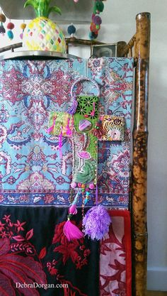 This arty wall hanging of a cross is the first of six, that finally got finished!....and is made of mostly vintage textiles with some beading, a raggedy pom pom, hot pink feather, hand painted tusk, a slice of pink Agate, a Paua shell tusk and some little hand made tassles. It is backed with a soft velveteen type fabric, in hot pink. It hangs from a lilac coloured raffia ring.  It has lots of detail and hand stitching and will make a sweet, kitschy addition to the home :-) It will look…