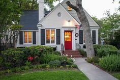 White cottage with shutters and red front door via Zillow