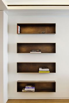 Backlit bronze shelves in the living room are inset into the walls and hold select books.