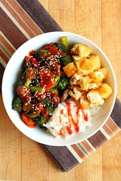 Garden of Vegan: Stir-fried veggies (broccoli, red bell pepper, carrots, and mushrooms with sriracha + soy sauce and topped with spicy sweet peanut sauce), short grain rice with sriracha, and deep-fried tofu puffs.