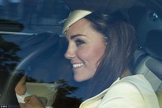 Glowing mother: Catherine, Duchess of Cambridge rubs the arm of her young son Prince George as he sits patiently in his car seat