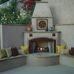 Outdoor living area with a fireplace featuring a ceramic tile Pomegranate mural.