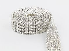 This is brand-new 4-row silver mesh ribbon. Perfect for decorating wedding cakes, centerpieces, clothing, accessories and so on. This product sparkles well in the light. This is made from coated plastic indents that reflect the light very well, giving the appearance of rhinestones. The ribbon may be cut in any direction without damaging it. Mesh can be cut, sewn, glued, hot glued and is perfect for most art and craft projects.  Material: Plastic Reflectors Color: Silver Stone Size: No Stones…
