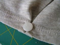 to tighten a sleeve, make a pleat and hide the stitches with a button