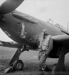 """""""Squadron Leader J A F MacLachlan, the one-armed Commanding Officer of No 1 Squadron RAF, standing beside his all-black Hawker Hurricane Mark IIC night fighter, 'JX-Q', at Tangmere, Sussex."""