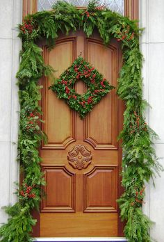Love the contrasting greenery and diamond shaped wreath to echo the emblem on the door. Holiday Outdoor Decorating Tips from Mariani Landscape - Traditional Home® Christmas Front Doors, Christmas Porch, Outdoor Christmas Decorations, Winter Christmas, All Things Christmas, Christmas Wreaths, Christmas Design, Xmas, Theme Noel