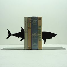 The Shark Bookends are a pair of solid metal bookends handmade by Knob Creek Metal Arts.